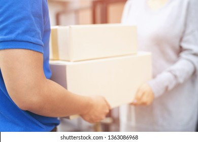 parcel delivery man of a package through a service. and close up hand customer female accepting a delivery of boxes from delivery man postal send direct to home.