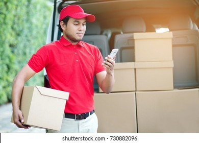 parcel delivery man stand use phone and contact the customer. counting Check stock Prepare to send the package to the customer. Validate every time in transportation.