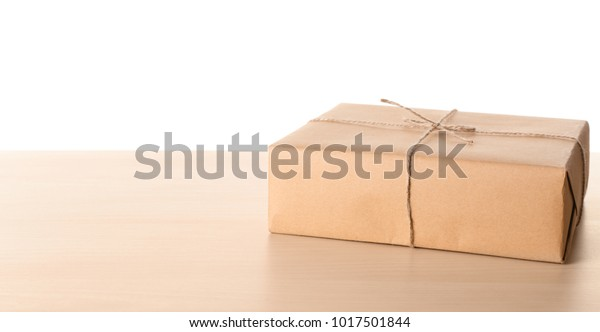 Parcel gift box on wooden table against white background