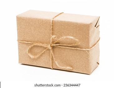 A parcel wrapped in brown paper and tied with rough twine. side view
