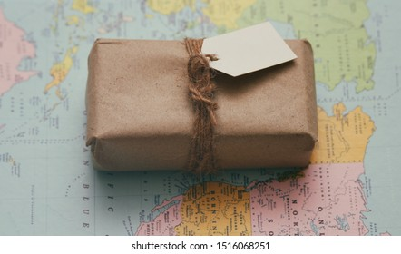 Parcel wrapping in brown craft paper and tie hemp string. Package with paper label. Delivery service. Online shopping. Your purchase. Gift box on a table. Blue solid background. Worldwide shipping.