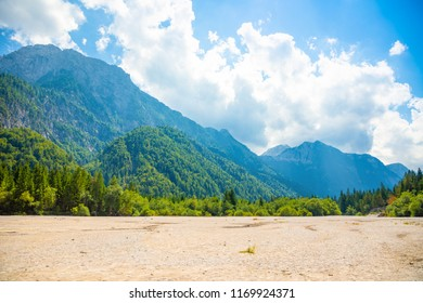 Parched bottom of Lake Predil with turquoise water and mountains in background near Tarvisio in European Alps in Italy
