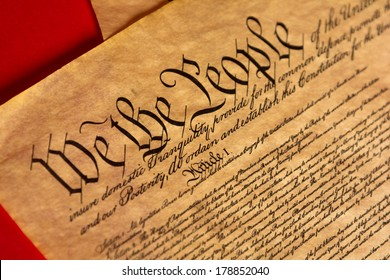 A parchment of the Constitution of the United States with a red background