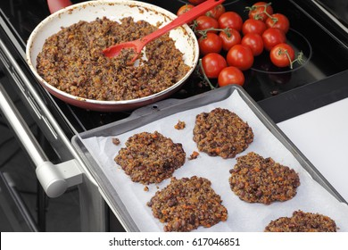 Parchment paper lined cookie sheet with quinoa and three bean patties ready to be cooked. Preparing tricolor bean and quinoa burgers recipe in the kitchen.