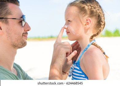 Parent applying sun cream to kid nose. Portrait of cute girl in suncream