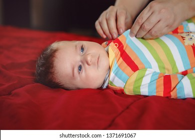 Parent caregiver changing diaper clothes for newborn baby boy girl laying on bed. Mother father taking care of child at home. Authentic lifestyle candid moment.