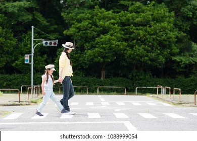 Parent and child crossing a pedestrian crossing