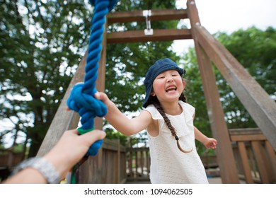Parent and child hand over the rope at the park