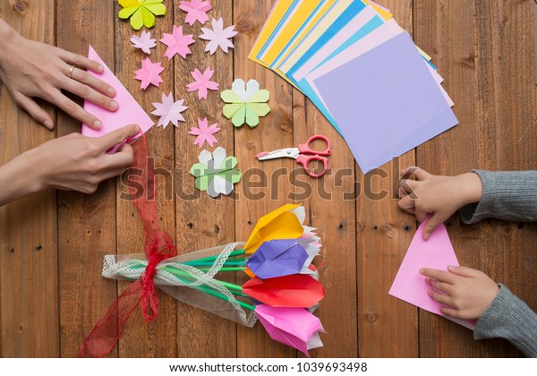 Parent and child hand playing with origami