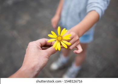 Parent and child handing over yellow flowers