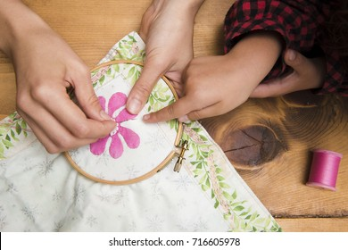 Parent and child hands to embroider