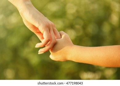 Parent and child holding hands outdoor