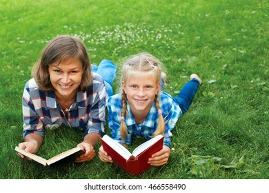 Parent and child reading books together in the park