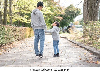 Parent and child walking with hands