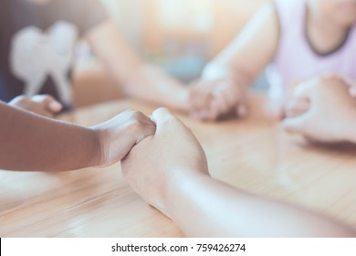 Parent and children holding hands and praying together on wooden table