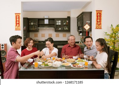 Parent, grandparents and children enjoying good food at Lunar New Year celebration, couplets with best wishes for coming year in the background