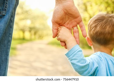 the parent holding the child's hand with a happy background