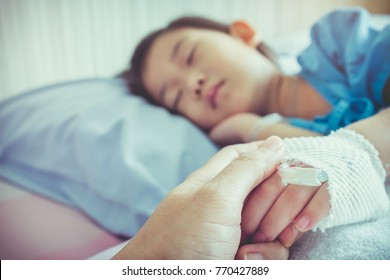 Parent holding child's patient hand for encouragement and empathy. Girl sleeping while saline intravenous drip on hand. Relationship and trust concept. Selective focus. Vintage film filter effect.