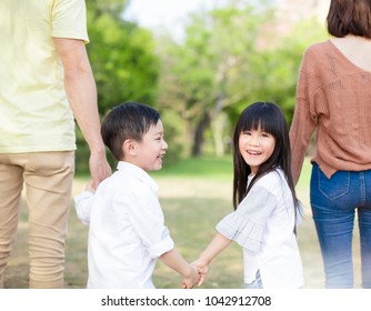 parent holds the hand of children