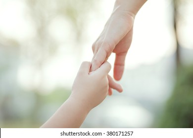 Parent holds the hand of a little child, soft focus, warm tone