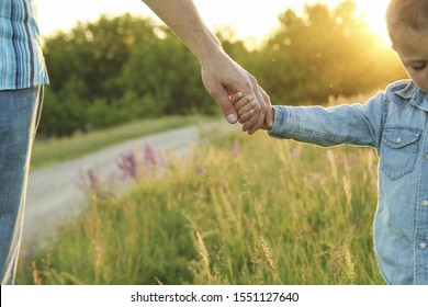 the parent holds the hand of a small childon nature