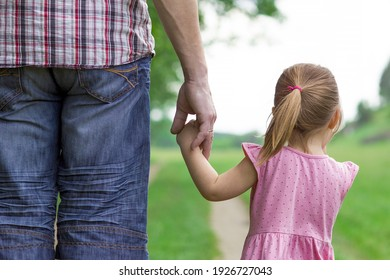 parent holds the hand of a small child and walk