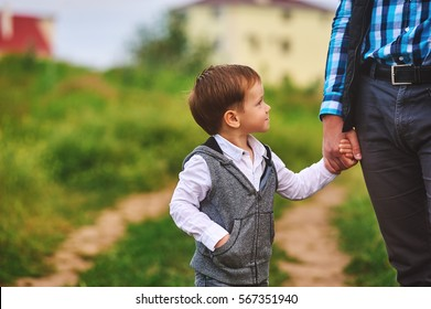 a parent holds the hand of a small child. Father's day