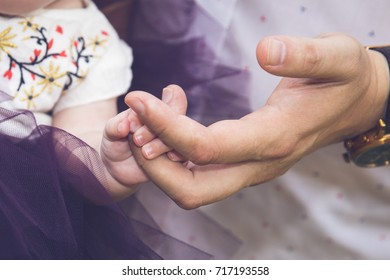 a parent holds the hand of a small child. Dady holding baby