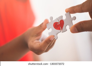 Parent and kid hands connecting couple jigsaw puzzle piece with drawn red heart
