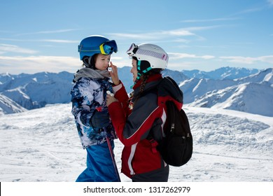 Parent, mother, putting sun cream on child's face on top of mountain, preparing him for a sunny day of skiing