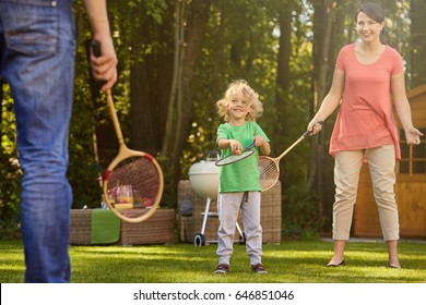 Parent playing badminton with their sweet little son