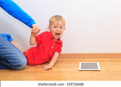 Parent pulling child from touch pad. Computer Addiction