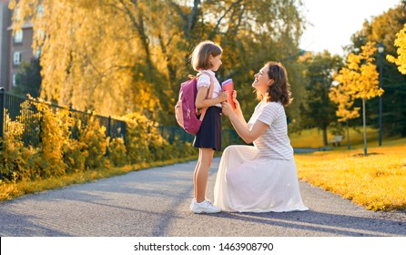 Parent and pupil of primary school go hand in hand. Woman and girl with backpack behind back. Beginning of lessons. First day of fall.