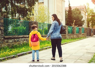 Parent and pupil of primary school go hand in hand. Woman and boy with backpack. Beginning of lessons. First day at school. Mother taking son to school. Mom supports her son before school.