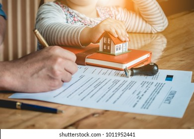 Parent signing at contract document for buy house with his daughter, first time home buyers, real estate purchase concept.