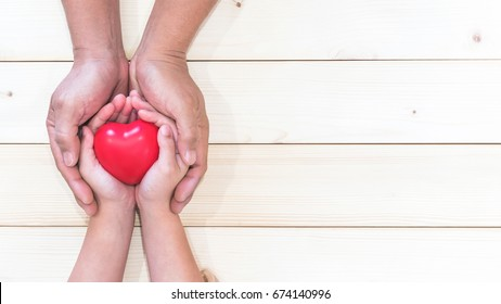 Parent supporting child's hands with red heart for I love you dad, Father's Day holiday celebration, csr charity donation, and home family nursing health care for kids healthcare insurance concept