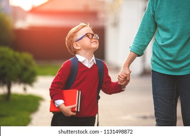 Parent take child to school. Pupil of primary school go study with backpack outdoors. Mother and son go hand in hand. Beginning of lessons. Back to school. First day of fall. Elementary student.