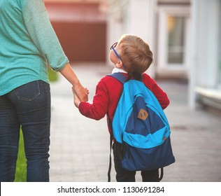 Parent taking child to school. Pupil of primary school go study with backpack outdoors. Mother and son go hand in hand. Beginning of lessons. Back to school. First day of fall. Elementary student.