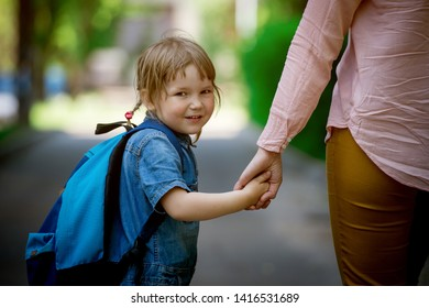 Parent taking child to school. Pupil of primary school go study with backpack outdoors. Mom and daughter go hand in hand. Beginning of lessons. Back to school. First day of fall. Elementary student.