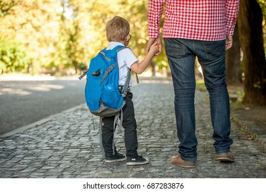 Parent taking child to school. Pupil of primary school go study. Father holding hand of little son with backpack outdoors Beginning of lessons. Back to school. First day of fall. Elementary student.