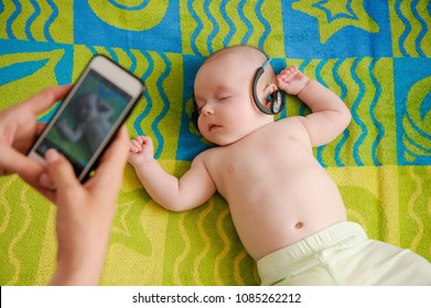 Parent taking photo of a baby with smartphone. Adorable newborn child sleeping on beach towel and listening to relaxing music in his dad's headphones. sucking feet. Digital family memories