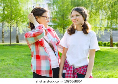 Parent and teenager, mother talks with her teen daughter 13, 14 years old. Background nature, park.
