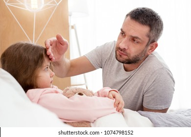 Parental care. Serious devoted daddy touching his girls forehead and the girl lying in bed