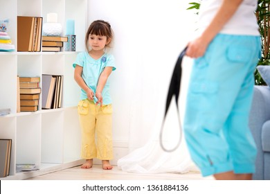 Parental punishment. Child abuse. Mom punish a little daughter with a belt and puts her in a corner. Don't hit the kids, help to protect children.