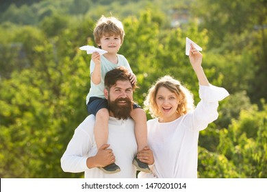 Parenthood and childhood concept. Father mother and his son playing outdoors. Father mother and son having fun and playing in nature. Father carrying his son on shoulders