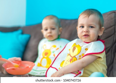 parenthood concept - mother with puree and spoon feeding little baby twins at home