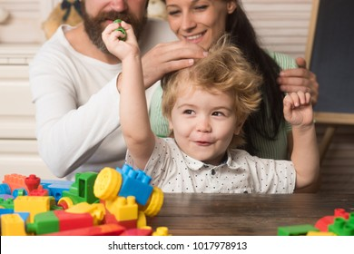 Parenthood concept. Parents watch their son hold constructions made out of colorful blocks. Kid smiling face plays with plastic bricks on light background. Family spend time together in playroom.