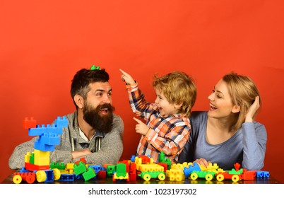 Parenthood and game concept. Man with beard, woman and boy play on red background. Kid and mom laugh at dad in playroom. Family with happy faces build toy cars out of colored construction blocks.