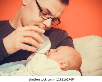 Parenting and love concept. Father holding and taking care of little newborn baby, feeding milk from bottle.