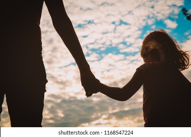 parenting -mother and daughter holding hands at sunset